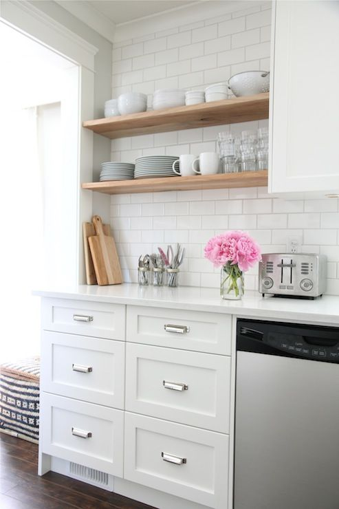 source: Our House   White kitchen with white shaker cabinets painted Benjamin Moore Cloud White accented with Restoration Hardware Duluth Pulls paired with white quartz countertops and Home Depot subway tile backsplash. Kitchen features stacked floating shelves filled with glassware and pottery.