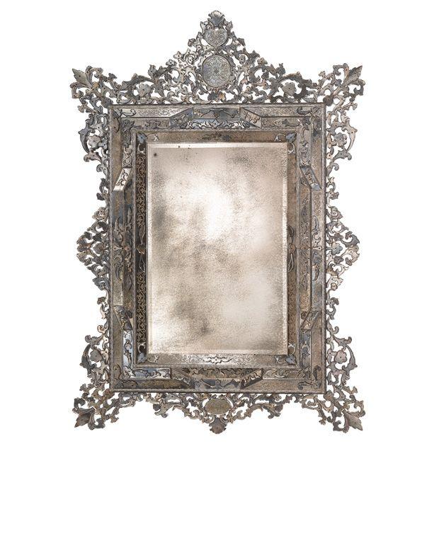 Importante specchio anticato in stile Veneziano traforo con incisioni floreali eseguite mediante mola diamantata a sfera. Trafori in specchio molato fissati con viti a vista. Telaio in legno massello anticato finitura bitume.