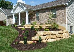 limestone retaining wall with dark mulch