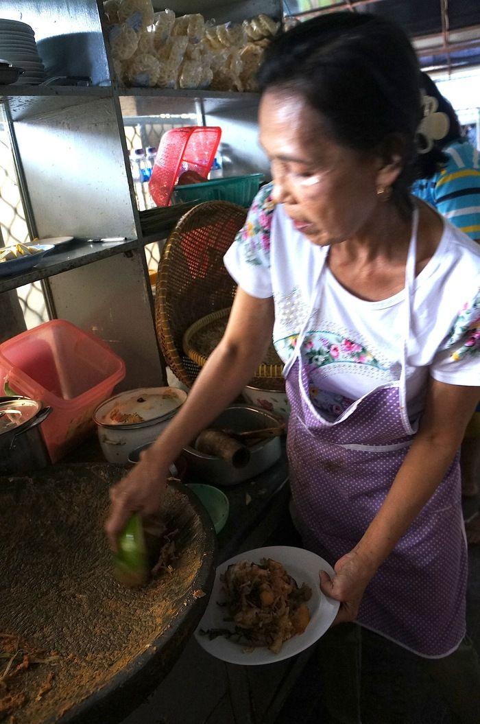 Ibu Rosihani uses young papaya to spoon the lotek into the plate. Photo by Icha Rahmanti.