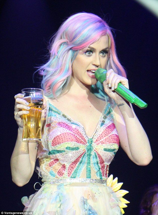 Cheeky drink: Katy made sure to raise a glass to the launch of her tour...