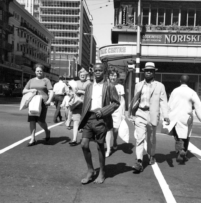 """People crossing a busy street in Johannesburg.  """"The stream goes over the street, but knowing Mpanza's son, he (Kumalo) is afraid to follow."""""""