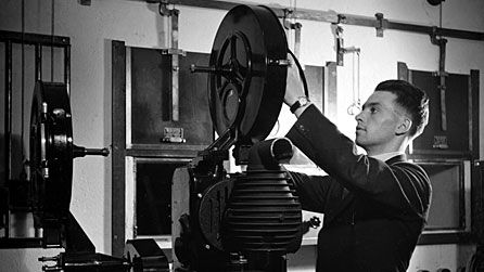 Type of document: Photograph  Date of origin: 1920  This is a photo of a man fixing the film inside a projector that was actually used in the 20s. This is a good example of how the 20s were roaring because entertainments was a huge part of the 20s, and films were very popular during that time as well (BBC).
