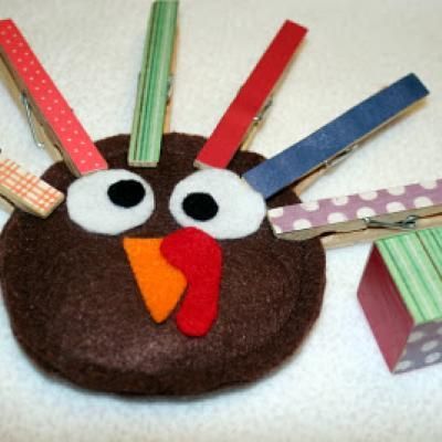 "Love this crazy turkey game for the kids! Mod Podge some scrapbook paper to clothespins, and make the turkeys out of felt.  (Brown head is batting sewn between two circles of brown felt.) Cover a block in paper to make the ""dice"" to roll.  First one to get all 6 ""feathers"" on his turkey wins."