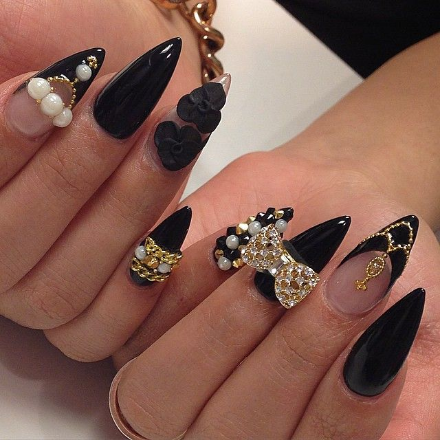 Black stiletto nails with gold bling and pearls