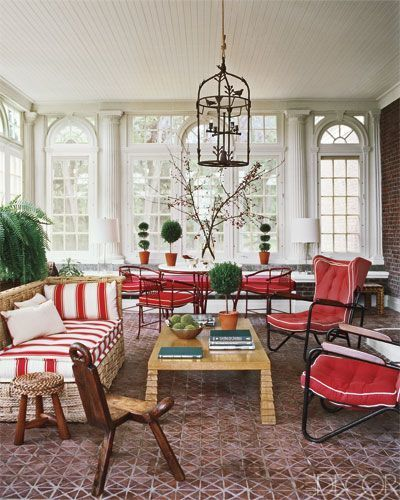 Red-and-white upholstery and an array of topiaries bring color to the grandly scaled sunroom of a Tuxedo Park, New York, home decorated by Ernest de la Torre. A woven-rattan chaise and vintage armchairs surround a Jean-Michel Frank-inspired cocktail table.   - ELLEDecor.com