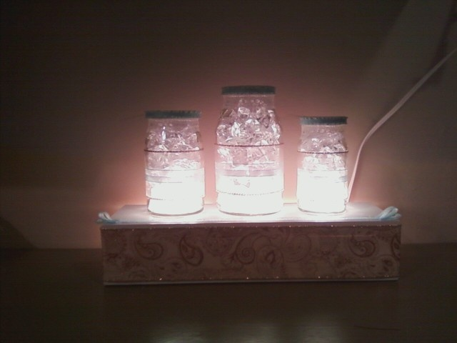 My kitchen night light:  Empty smuckers jars, under-cabinet lights, pretty ribbon, glass rocks and some wood (for the box I mounted the lights in).