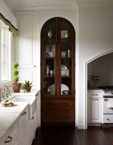 El cristalero de madera oscura le da contraste a la blanca cocina ...