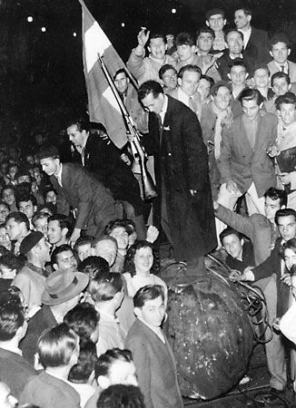 A crowd gathering around a toppled statue during the 1956 Hungarian uprising in Budapest.  Credit: Keystone/Hulton Archive/Getty Images