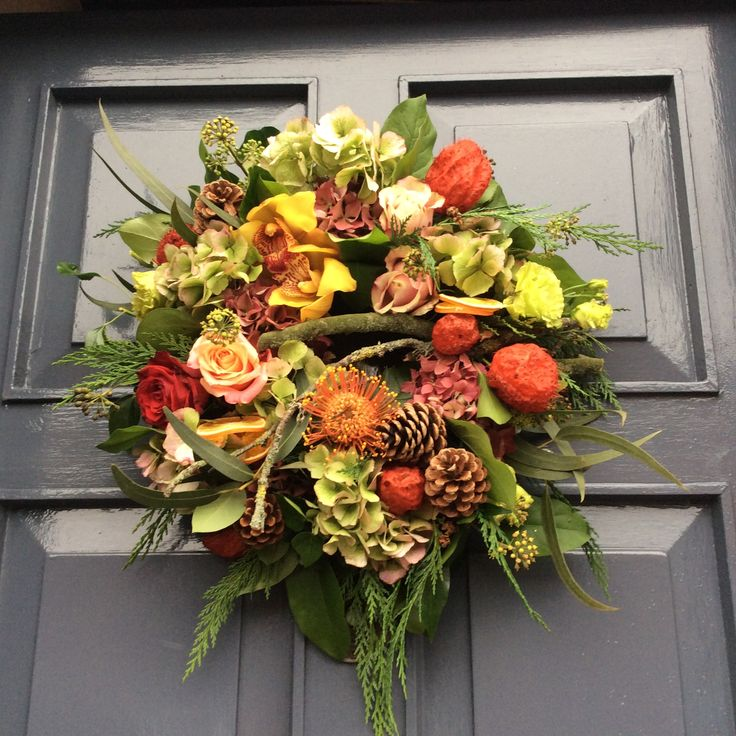 Fresh Christmas door wreath in reds and oranges hand made using orchids, hydrangea, nutan, pine cones, roses and foliages