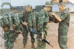 H Company Rangers gearing up for a mission. The man on the right is checking the M3 medic bag carried by the Ranger at second right. Note the green dominant ERDL uniforms, two M72 LAWs, and tropical rucksacks.