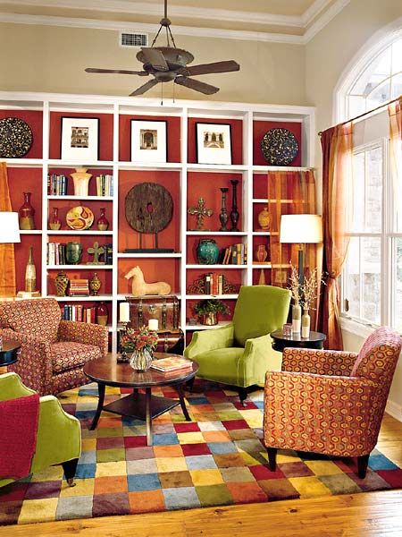 This comfortable living room has two large arched openings that fully connect it to the rest of the house. The bookshelves are framed by a wire curtain rod and sheer panels, which work to give the plain built-ins some pizzazz and to soften their appearance. Adjustable shelves allow for different-size collectibles, while a rust-colored accent wall behind them helps to highlight their contents. (Photo: Photo: Van Chaplin; Stylist: Lisa Powell)