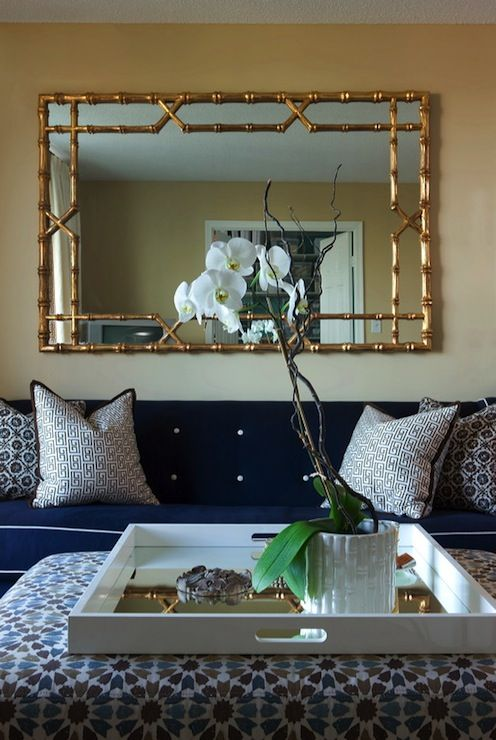 living rooms - orchid blue sofa white piping gold walls gold faux bamboo mirror white black Greek key pillows white blue green floral upholstered ottoman glossy white mirrored tray orchid