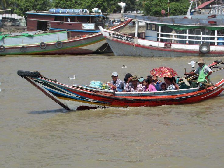 Long tail boats shuttle across the Yangon River (also known as the Hlaing River) between Yangon, Myanmar (Burma). and Dalah