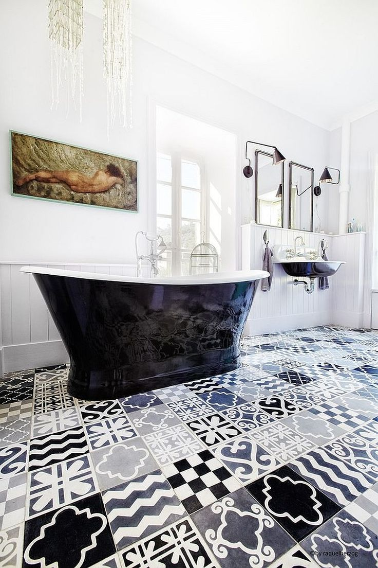 Bagno in bianco e nero con un mosaico di piastrelle a motivi geometrici