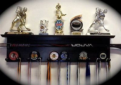 Hockey Trophy & Award Display Shelf - This custom, hand-crafted wood shelf is designed for the hockey player/parent who needs a place to showcase his/her favorite stick, trophies, medals, ribbons, awards, puck collection (holds 10), collectibles, picture frames and more! Available in Black, Natural or White.