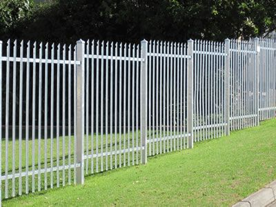 White steel palisade fence in ladder type, installed on the grass land, the…