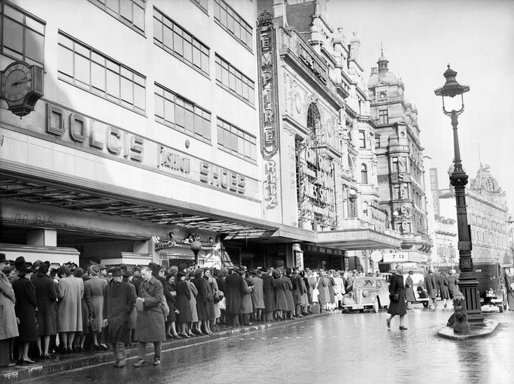 A busy scene in London's Leicester Square, 1941, as civilians and service personnel queue for admission to the Empire and Ritz cinemas. The queue snakes past a large Dolcis shoe shop and a small milk bar before reaching the cinemas. The Empire is showing 'The Philadelphia Story', starring Cary Grant, Katharine Hepburn and James Stewart, whilst the Ritz appears to be showing 'Gone with the Wind'.