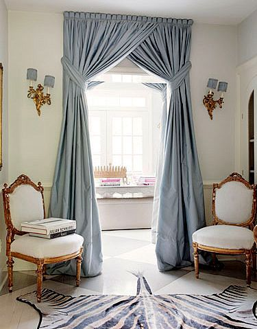 Curtains -- when hung somewhere other than a window -- add softness, color, movement, and perhaps a subtle sense of enclosure or privacy in a space.