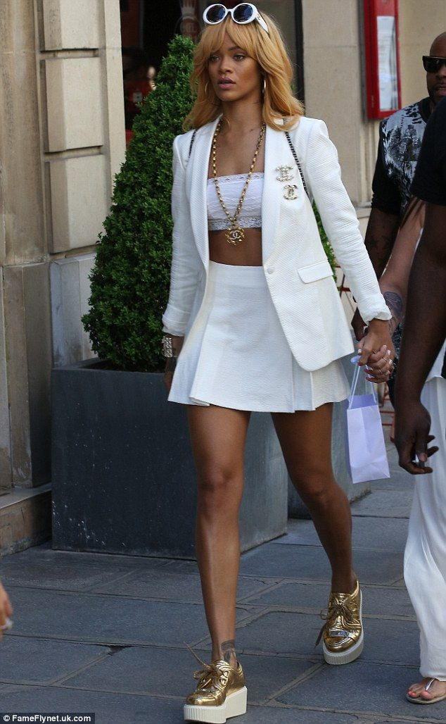 Ready for tennis: Rihanna would have fit right in at the French Open in a white skirt, cropped top and gold trainers while shopping in Paris on Tuesday