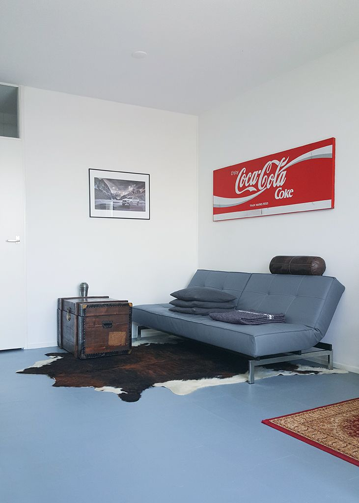 Living room sitting area. Vintage sign by Coca-Cola, an antique travel trunk, and a 'Splitback' sofa bed by Innovation. Cow skin rug and leather pillow by DOM. Army blanket by Merci Paris and off-the-shelf grey pillows. Lamp by MetalArte, type 'ZEN'. Black frame with digital artwork.