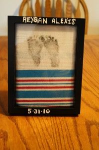 Use the blanket given to you by the hospital (or any blanket really), using black ink, imprint your child's footprints onto the blanket. Frame it (you need a deeper frame like a shadowbox), and use a paint pen to write on the frame with the name and DOB.