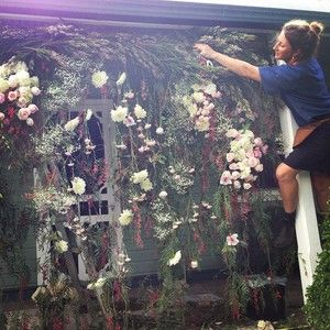 This is how we do it! Mel creating magic yesterday for the ceremony flower wall-arch #littlewrenflowerswedding #hangingflowers #flowerwall #arch #flowerarch #brokewedding #johnlovesgeorge