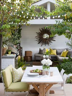 Unexpected Mix: A rustic, farm-style table is paired with two white modern chairs and a contemporary outdoor love seat.