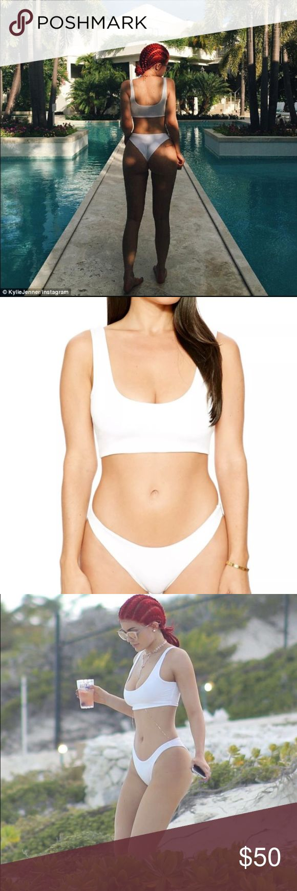 Naked Wardrobe crop top white bikini set ASO Kylie New with tags attached Naked Wardrobe white bikini set. The bikini has a zipperless pull on construction and the bikini bottoms are a Brazilian cut which compliments the crop top bikini top nicely. Both pieces are lined, and not see thru at all. The set has been worn by Kylie Jenner and multiple Kardashian fashionistas. Get the same exact brand and bikini as Kylie for a fraction of the original MSRP! Naked Wardrobe Swim Bikinis
