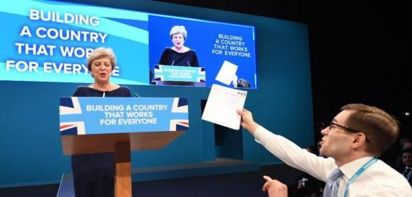 During a speech Wednesday to the Conservative Party in London, British leader Theresa May was interrupted by a heckler serving her with a…
