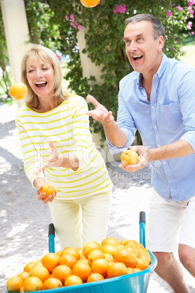Старший пара, жонглирование апельсинами перед тачку