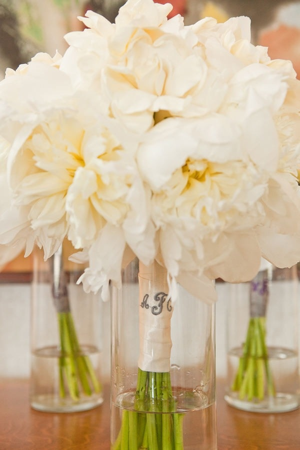 Love the all white/cream peonies and/or dahlias for the bridesmaids with monogrammed ribbon -- doubles as additional floral on the reception tables