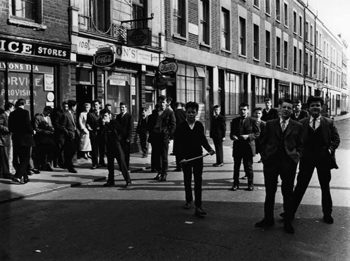 Turning the corner into Princedale Road, North Kensington, Roger Mayne saw a group of young Teddy Boys whom he thought 'a bit sinister'. Crossing to the opposite side, he had got past them when one called out, 'Take our photo, Mister!'. Mayne turned around and took a number of photos - he 'wasn't going to miss a chance like that'.