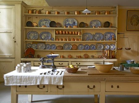 The Kitchen in the basement at Uppark, West Sussex. The table holds a selection of cooking utensils with the dresser behind containing blue and white china and copper moulds and saucepan.