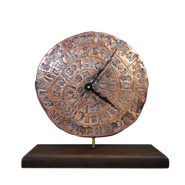 The Phaistos Disc, the unique archaeological find from Phaistos in Southern Crete and one of the most famous mysteries of ancient greek art, inspired us to create an aesthetic clock, made of copper. The unique clock has embossed symbols of the disc and stands on a wooden base. 17th century B.C., Phaistos, Crete Dimensions of the disc: 17 cm x 7 mm Dimensions with wooden base: 20 cm x 19,5 cm x 5,5 cm Copper with wooden base.