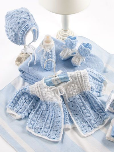 """New from Annie's! Girls' set by Michelle Crean includes a beautiful white christening gown with puff sleeves embellished with a crocheted lace edging, matching booties, bonnet and bottle cover. The boys' set includes a dashing blue sweater with a white yoke and a matching bonnet, booties and bottle cover all trimmed in white. Both sets are sizes for 0-3 months and 3-6 months. The blanket is 36"""" x 43 1/2"""" and is stitched in white to compliment both ensemb"""