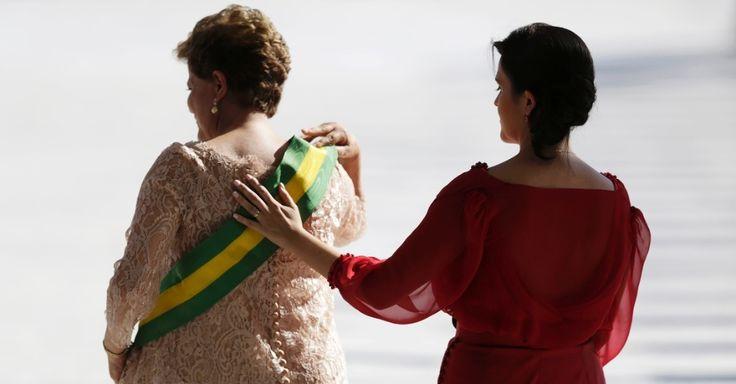 1 jan 2015 - a filha da presidente Dilma Rousseff, Paula, ajeita a faixa presidencial de Dilma após a presidente recebe-la na rampa do palacio do planalto