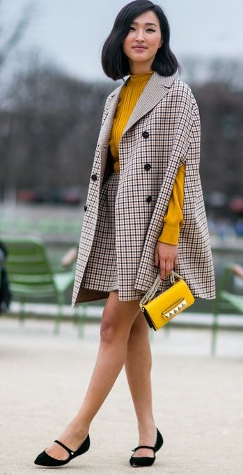 Nicole Warne at Paris Fashion Week wearing a plaid cape and matching skirt with a yellow turtleneck and studded purse