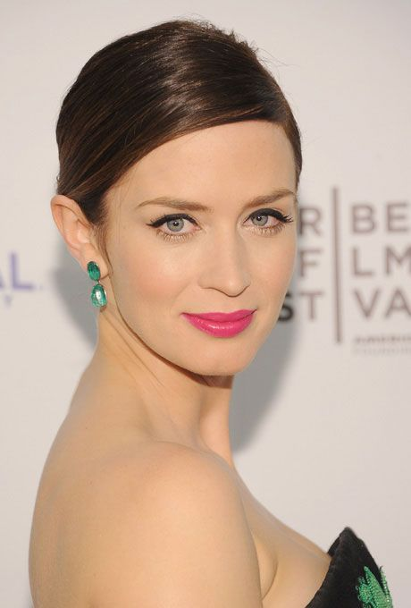 Brides.com: Hot Pink Wedding Makeup Made Simple. Red carpet regular Emily Blunt gives her lips an extra pop by juxtaposing a fuchsia pout with emerald earrings. A sleek, minimal bun focuses the attention on her pretty visage.