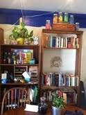 bookshelves with homemade aromatherapy rainbow play dough, chalk and face paints, modeling beeswax, watercolor and fingerpaint supplies, abacus, number cards, pastels, beeswax crayons, french flash cards, and Grimm's Spiel und Holz magnet game