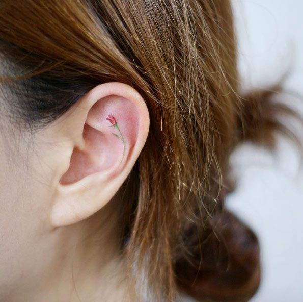 Tiny rose ear tattoo by Doy