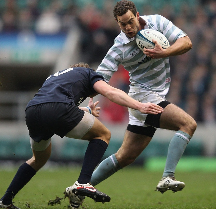 Cambridge's Robert Stevens is tackled by Oxford's Tom Mitchell