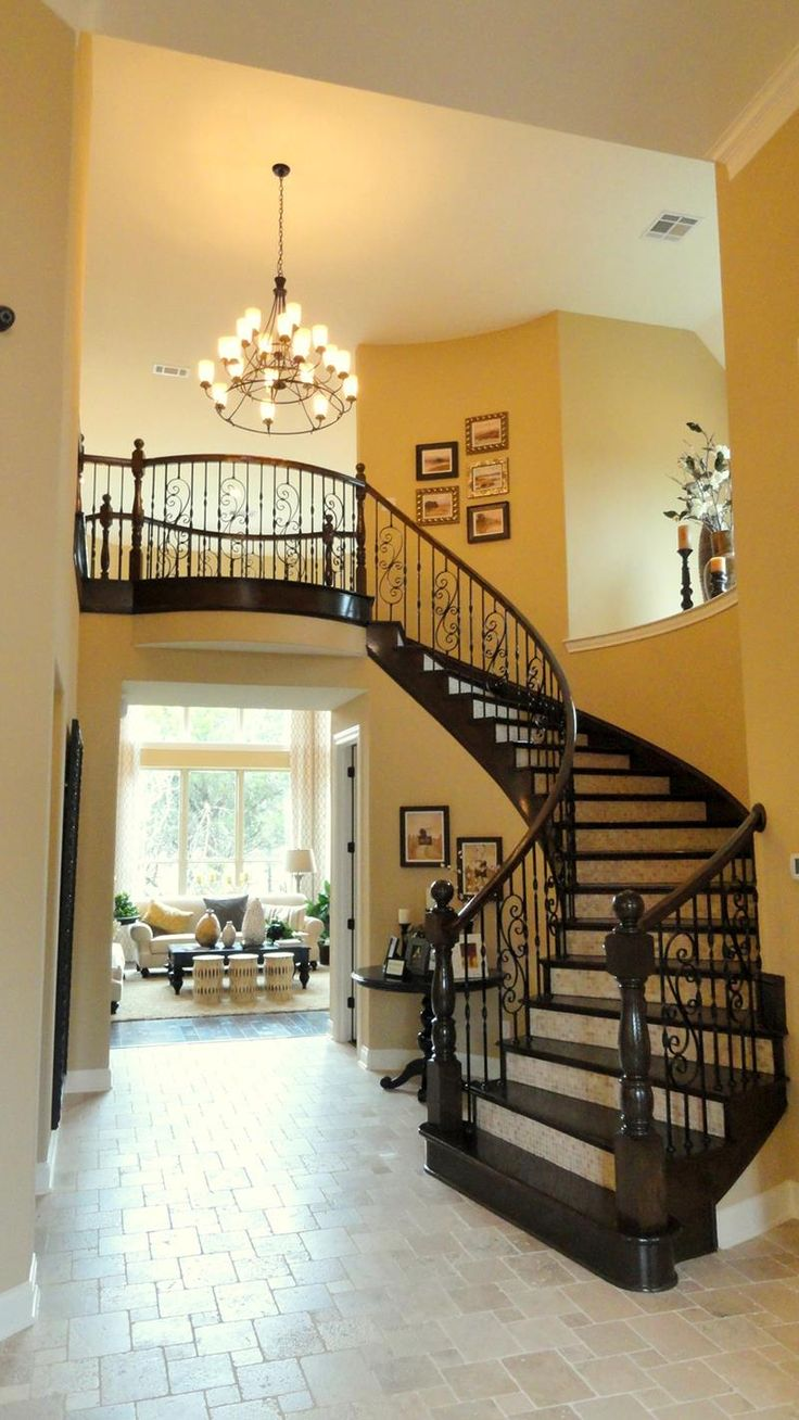 The dark hardwood helps the curved staircase in this luxury foyer pop out, creating an unmistakable impression.