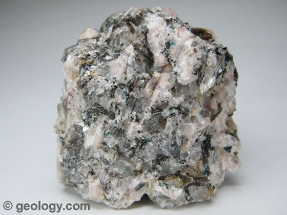 Pegmatite is a light-colored, extremely coarse-grained intrusive igneous rock. It forms near the margins of a magma chamber during the final phases of magma chamber crystallization. It often contains rare minerals that are not found in other parts of the magma chamber. The specimen shown above is about two inches (five centimeters) across.