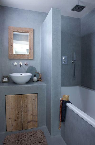 L'astuce gain de place : pour cette salle de bains de poche habillée de béton ciré, non seulement il y a de la place pour une baignoire, mais il y en a aussi pour une douche ! La solution ? Une baignoire deux en un. Ici, un combiné de douche encastré a simplement été installé au-dessus de la baignoire, et le petit mur adjacent au lavabo sert de paroi de douche.