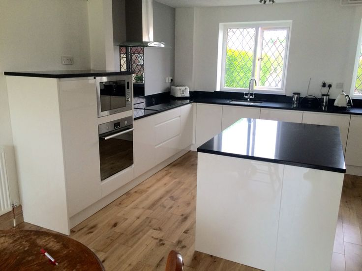 Remo White gloss handless doors with Compac Quartz work surfaces.