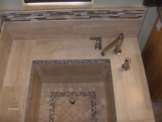 Roman Tub With Porcelain Tile And Glass Stone Details In