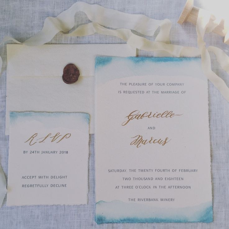 Beautiful beach theme wedding invitations. Dusky blue watercolour wash with gold calligraphy on hand made paper.