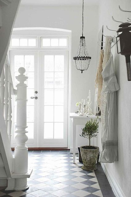 wonderful, inviting entryway.  I like the white soothing colors, natural light from the French doors and the black and white tiled floor (of which I would love to have someday in my own foyer!)