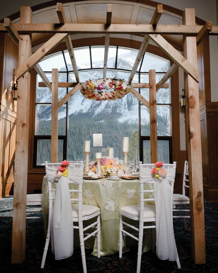 Suspended florals in peach, pink, yellow and ivory tones at the Fairmont Chateau Lake Louise as seen in the Calgary Bridal Guide.  Photo: www.hugephotography.com Decor/Planning: www.mountainbride.com Florals: www.flowersbyjanie.com  #Fairmontchateaulakelouise #mountainweddings #Banffweddingflorist #FlowersbyJanie